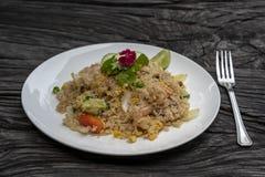 Το τηγανισμένο ρύζι με τις γαρίδες και τα λαχανικά σε ένα άσπρο πιάτο σε έναν παλαιό ξύλινο πίνακα, κλείνει επάνω Ταϊλανδικά τρόφ στοκ εικόνα με δικαίωμα ελεύθερης χρήσης