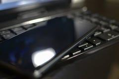 Το τηλέφωνο στηρίζεται στο πληκτρολόγιο lap-top Στοκ φωτογραφία με δικαίωμα ελεύθερης χρήσης