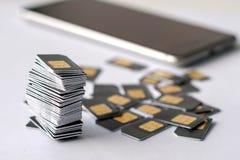 Το τηλέφωνο στο υπόβαθρο στο πρώτο πλάνο ένας σωρός της συγκεντρωμένης κάρτας SIM είναι γκρίζο Στοκ εικόνες με δικαίωμα ελεύθερης χρήσης