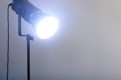Το τηλεοπτικό φως κινηματογραφήσεων σε πρώτο πλάνο λάμπει στεμένος στο μαύρο τρίποδο Στοκ Εικόνα
