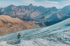 Το τολμηρό άτομο στέκεται πάνω από το βουνό και απολαμβάνει την όμορφη θέα κατά τη διάρκεια ενός δονούμενου ηλιοβασιλέματος στοκ εικόνες