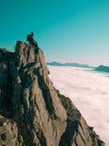 Το τονισμένο ενήλικο άτομο εικόνας με τη συνεδρίαση σακιδίων πλάτης, πόδια που ταλαντεύει στην άκρη ενός απότομου βράχου και εξετ Στοκ Φωτογραφίες