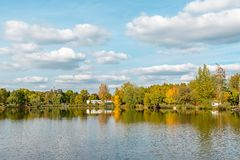 Το τοπίο με τη λίμνη, το νεφελώδη ουρανό, και τα δέντρα απεικόνισε symmetrically στο νερό Αλατισμένη λίμνη Sosto Nyiregyhaza, Ουγ στοκ φωτογραφίες