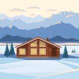 Το τοπίο χειμερινών βουνών με το ξύλινο σπίτι, σαλέ, χιόνι, φώτισε τις αιχμές βουνών, ποταμός, δέντρα έλατου, φωτισμένα παράθυρα ελεύθερη απεικόνιση δικαιώματος