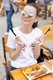 Το τοπικό φεστιβάλ τροφίμων Ένα όμορφο κορίτσι τρώει τα τηγανισμένα λουκάνικα και τα λαχανικά Στοκ Φωτογραφίες
