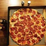 Το τοπ επίπεδο άποψης βάζει μιας μεγάλης λεπτής Pepperoni κρουστών πίτσας με τα accompaniments Στοκ φωτογραφία με δικαίωμα ελεύθερης χρήσης