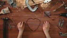 Το τοπ χρόνος-σφάλμα άποψης μιας τοποθέτησης χεριών επάνω η επιτραπέζια μορφή της καρδιάς με τις βίδες απόθεμα βίντεο