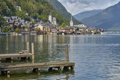 Το του χωριού τοπίο Hallstatt με τα παλαιά κτήρια απεικόνισε στην μπλε λίμνη με τις ξύλινες γέφυρες στο πρώτο πλάνο στοκ φωτογραφία με δικαίωμα ελεύθερης χρήσης