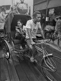 Το τρίκυκλο και η γυναίκα γύρου ανδρών είναι επιβάτης στην αγορά Στοκ εικόνα με δικαίωμα ελεύθερης χρήσης
