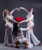 Το τρίο όμορφου πηγαίνω-πηγαίνει χορευτές που θέτουν ως cupids Στοκ Φωτογραφία