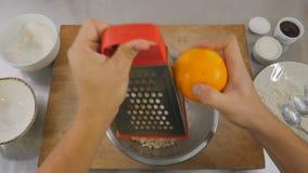 Το τρίψιμο μαγείρων σε έναν ξύστη το πορτοκάλι για την τηγανίτα τυριών φιλμ μικρού μήκους