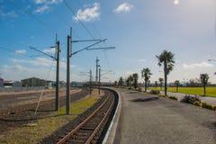 Το τραίνο ακολουθεί τον πόλο ηλεκτροφόρων καλωδίων και δύναμης Στοκ Φωτογραφία