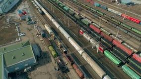 Το τραίνο πηγαίνει στις διαδρομές σε σε αργή κίνηση Πολλά τραίνα στο υπόβαθρο Το εναέριο βίντεο παρουσιάζει μεγάλη αποθήκη τραίνω απόθεμα βίντεο