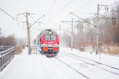 Το τραίνο σιδηροδρόμου έρχεται έξω από το χιονώδη καιρό Στοκ Εικόνα