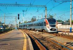 Το τραίνο υψηλής ταχύτητας φθάνει στο σιδηροδρομικό σταθμό στο ηλιοβασίλεμα στοκ φωτογραφία