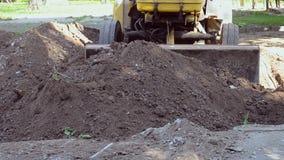 Το τρακτέρ αφαιρεί τον εδαφολογικό ρύπο, σκάβει το εργοτάξιο οικοδομής τρυπών απόθεμα βίντεο