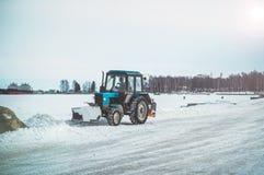 Το τρακτέρ καθαρίζει το ανάχωμα από το χιόνι στοκ εικόνα