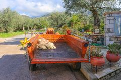 Το τρακτέρ και το ρυμουλκό με την ελιά μαζεύουν με τη τσουγκράνα και pruner σταθμευμένος στο ελληνικό χωριό με τα άλση ελιών στη  στοκ εικόνες με δικαίωμα ελεύθερης χρήσης