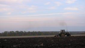 Το τρακτέρ καλλιεργεί το μαύρο χώμα το βράδυ απόθεμα βίντεο