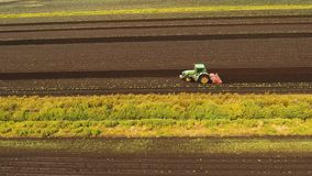 Το τρακτέρ καλλιεργεί το έδαφος στον τομέα φιλμ μικρού μήκους
