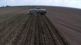 Το τρακτέρ με τον καλλιεργητή καλλιεργεί το έδαφος σε έναν τομέα Εναέριο μήκος σε πόδηα - που πετά πέρα από ένα τρακτέρ σε έναν τ φιλμ μικρού μήκους