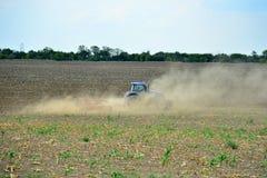 Το τρακτέρ οργώνει τις μύγες γης και σκόνης στις διαφορετικές κατευθύνσεις, προετοιμάζοντας το έδαφος για τη σπορά στο oen στοκ φωτογραφία με δικαίωμα ελεύθερης χρήσης