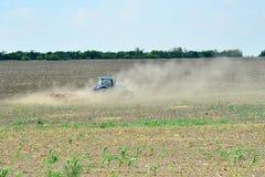 Το τρακτέρ οργώνει τις μύγες γης και σκόνης στις διαφορετικές κατευθύνσεις, προετοιμάζοντας το έδαφος για τη σπορά στο oen στοκ φωτογραφίες με δικαίωμα ελεύθερης χρήσης