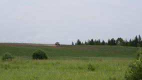 Το τρακτέρ οργώνει τον τομέα γεωργικά μηχανήματα σε έναν ορίζοντα απόθεμα βίντεο