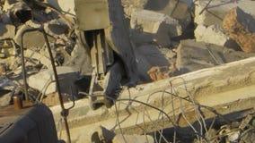Το τρακτέρ συνθλίβει έναν τσιμεντένιο ογκόλιθο στις καταστροφές του κ απόθεμα βίντεο