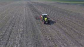 Το τρακτέρ ταξιδεύει γρήγορα πέρα από τον τομέα, καλλιεργεί τη γη έτσι ώστε η υγρασία δεν χάνεται την αεροφωτογραφία φιλμ μικρού μήκους