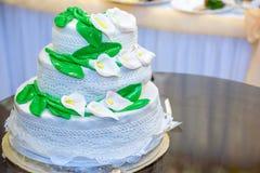 Το τρεις-τοποθετημένο στη σειρά γαμήλιο κέικ είναι διακοσμημένο με τα λουλούδια και στέκεται στον πίνακα δίπλα σε ένα πιάτο και μ Στοκ Εικόνα