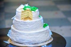 Το τρεις-τοποθετημένο στη σειρά γαμήλιο κέικ είναι διακοσμημένο με τα λουλούδια και στέκεται στον πίνακα δίπλα σε ένα πιάτο και μ Στοκ φωτογραφία με δικαίωμα ελεύθερης χρήσης