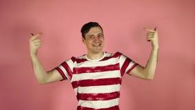 Το τρελλό άτομο πηδά και χαμογελά, παρουσιάζοντας χέρια του σε τον, σε ένα ρόδινο υπόβαθρο απόθεμα βίντεο