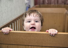 Το τριχωτό μωρό κλίνει στο σπορείο και χαμογελά στοκ φωτογραφίες με δικαίωμα ελεύθερης χρήσης