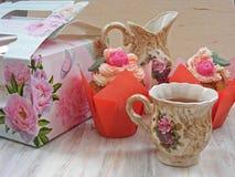 Το τσάι απογεύματος εξυπηρέτησε με ένα λουλούδι cupcakes και την εκλεκτής ποιότητας φλυτζάνα τσαγιού στο shabby υπόβαθρο στοκ φωτογραφία με δικαίωμα ελεύθερης χρήσης