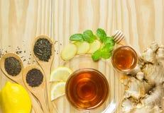 Το τσάι με την πιπερόριζα μελιού μεντών και λεμόνι στο ξύλινο υπόβαθρο, θερμός τόνος Στοκ Εικόνες