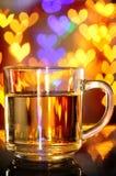 Το τσάι παράδοσης σε μια κούπα του γυαλιού με το φως καρδιών bokeh μειώνεται Στοκ Εικόνες