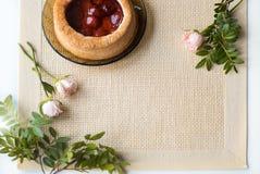 Το τσάι πρωινού με τα ψημένα αγαθά, αυξήθηκε λουλούδια στον πίνακα Κέικ με τις φράουλες Σε μια παλαιά πετσέτα Στοκ Φωτογραφίες
