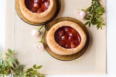 Το τσάι πρωινού με τα ψημένα αγαθά, αυξήθηκε λουλούδια στον πίνακα Κέικ με τις φράουλες Σε μια παλαιά πετσέτα Στοκ Εικόνα