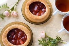 Το τσάι πρωινού με τα ψημένα αγαθά, αυξήθηκε λουλούδια στον πίνακα Κέικ με τις φράουλες Σε μια παλαιά πετσέτα Στοκ εικόνα με δικαίωμα ελεύθερης χρήσης