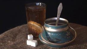 Το τσάι χύνεται στο γυαλί, το παλαιά κύπελλο ζάχαρης και burlap σε ένα μαύρο υπόβαθρο φιλμ μικρού μήκους