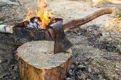 Το τσεκούρι στο κούτσουρο και ξύλο ενάντια στην πυρκαγιά σχαρών για το μαγείρεμα BBQ του κρέατος Υπαίθριο πικ-νίκ στοκ φωτογραφία με δικαίωμα ελεύθερης χρήσης