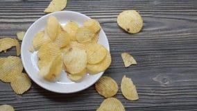Το τσιπ πατατών τηγάνισε τα πατατάκια στο πιάτο στον ξύλινο πίνακα, ορεκτικό τροφίμων πρόχειρων φαγητών με εύγευστος και νόστιμος απόθεμα βίντεο