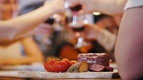 Το τυρί και οι ντομάτες λουκάνικων είναι στον πίνακα Οι φίλοι ξοδεύουν μια γιορτή φιλμ μικρού μήκους