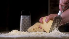 Το τυρί ΤΡΙΒΕΙ αργά σε έναν ξύστη μετάλλων σε έναν ξύλινο πίνακα Κοντά σε πολύ ξυμένο γιο o Η έννοια του μαγειρέματος των συστατι απόθεμα βίντεο
