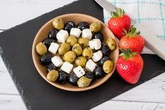 Το τυρί φέτας με τις πράσινες και μαύρες ελιές και τις φράουλες εξυπηρέτησε σε ένα κύπελλο στοκ εικόνα με δικαίωμα ελεύθερης χρήσης