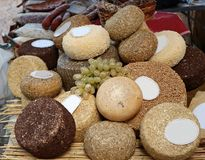 Το τυρί Pecorino κυλά καρυκεμμένος και που τυλίγει στο σανό ή τα σιτάρια σε ένα ράφι στην αγροτική αγορά στοκ εικόνα
