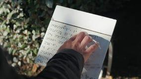 Το τυφλό κορίτσι ή το άτομο διαβάζει το κείμενο που γράφεται στον ηλιόλουστο πίνακα οδών ημέρας πηγών μπράιγ Άνθρωποι στις διακοπ φιλμ μικρού μήκους