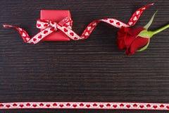 Το τυλιγμένο δώρο με την κόκκινη κορδέλλα και αυξήθηκε για την ημέρα βαλεντίνων, διάστημα αντιγράφων για το κείμενο Στοκ Φωτογραφία