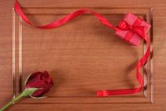 Το τυλιγμένο δώρο με την κόκκινη κορδέλλα και αυξήθηκε για την ημέρα βαλεντίνων, διάστημα αντιγράφων για το κείμενο Στοκ εικόνες με δικαίωμα ελεύθερης χρήσης